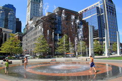 Children playing in water fountain pn busy city block,Boston,Massachusetts,Summer,2013 Stock Images