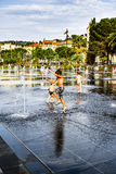 Children playing with water fountain Stock Image
