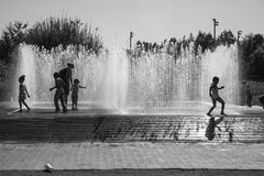 Children playing with water jets in the fountain stock photo