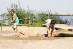 Children playing with water and sand Stock Photography