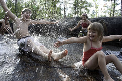 Children playing in waterfall stock images