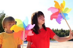 Children playing with windmill. Half body portrait of young boy and girl playing with colorful windmill toys on beach Royalty Free Stock Photos