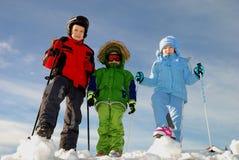 Children playing in winter. Three children standing with ski poles in winter snow stock photo