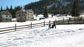 Children are Playing Winter Game Together Outdoors. Two Girls and One Boy are Rolling a Big Snowball up the Hill During. Warm Sunny Weather, HD stock video footage