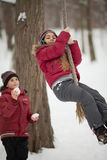 Children playing in winter park. Preadolescent girl and boy have fun with snowball and rope outdoors Stock Photo