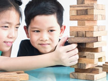 Children are playing a wood blocks tower game royalty free stock photography