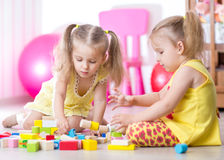 Children playing with wooden blocks sitting on the Stock Photos