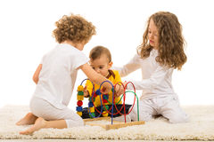 Children playing with wooden toy home. And sitting together on fur carpet royalty free stock photography