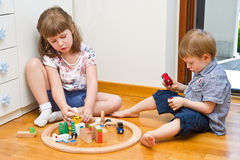 Children playing with wooden train in the room Royalty Free Stock Images
