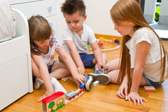 Children playing with wooden train in the room Royalty Free Stock Photo