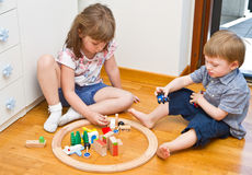 Children playing with wooden train in the room Stock Photography
