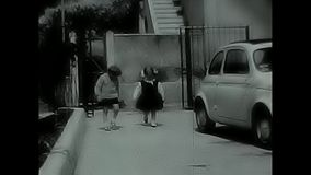 Children playing in the yard. Rome, Italy - Circa 1960 - children playing in the courtyard of a building where cars of the time are parked. Shooting carried out stock video footage