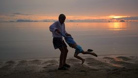 The children plays gleefully along the beach at sunset stock footage