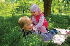 Children plays in green grass Stock Photos