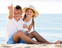 Children pointing with finger on sandy beach Stock Photos