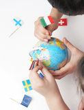 Children pointing flags on world globe Stock Photo