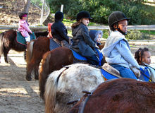 Children on ponies, ready to play. Children having hobby of pony riding.  At the pony riding center, during an outside pony riding class.  Playing, having fun Royalty Free Stock Photography