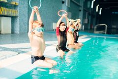 Children at pool. Children sits near pool and doing sportive exercises. Sporty kids with swimming goggles. Boys doing exercise in sweeming pool. Clean blue water Royalty Free Stock Images