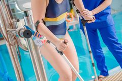 Children Pool Rehabilitation. Practitioner Physician Helping Disabled Girl To Reach the Swimming Pool By Special Chair Lift. Caucasian Disabled Girl. Physical stock images