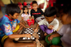 Children from poor areas in play chess Stock Images