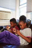 Children With Poor Diet Eating Meal On Sofa At Home Royalty Free Stock Photo