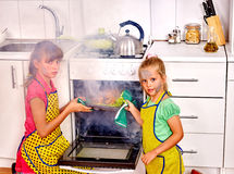 Children poorly cooking chicken at kitchen. Children with a burnt cooking chicken in the kitchen. Smoke. Faces of the children smeared with soot Stock Photo