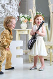 Children in pop retro suit laugh and playing the guitar Stock Images