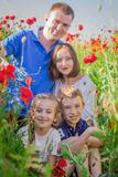 Children among poppy field with parents out of focus Stock Photography