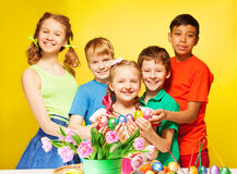 Children portrait who hold Eastern eggs and smile. Near the table with tulips and coloured eggs stock photos
