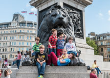 Children posing with Trafalgar Square lion Royalty Free Stock Photography