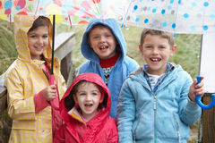 Children posing with umbrella Stock Image