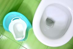 Children potty near the toilet. Training for pee and poo in adult toilet concept. stock images