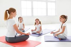 Children practicing engaged in gymnastics and yoga with teacher. Children practicing are engaged in gymnastics and yoga with teacher stock photo