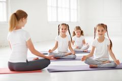 Children practicing engaged in gymnastics and yoga with  teacher Stock Photo