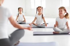 Children practicing yoga in a lotus pose with  teacher Stock Photos
