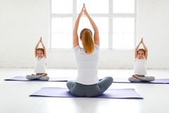 Children practicing yoga in a lotus pose with teacher stock images