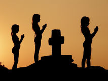 Children prayer. Three girls (kids-best friends) - silhouettes praying with folded hands beside the cross in a beautiful sunset Stock Image