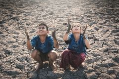 Children praying for the rain on lake. Concept drought and shortage of water crisis Stock Images
