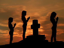 Children praying at sunset. Children (sisters) praying with clasped hands near the cross at wonderful sunset and sky Stock Photos