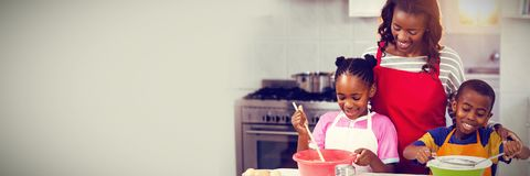 Children preparing cake with mother. In kitchen Royalty Free Stock Photos