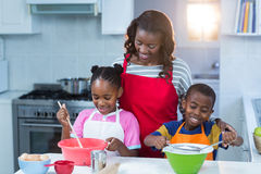 Children preparing cake with their mother Royalty Free Stock Images