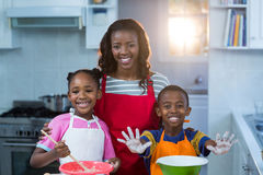 Children preparing cake with their mother Stock Photography