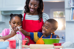 Children preparing cake with their mother Stock Photos