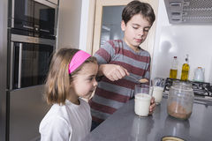 Children preparing a glass of milk Stock Photography