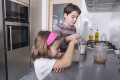 Children preparing a glass of milk Royalty Free Stock Images