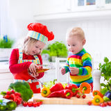 Children preparing healthy vegetable lunch. Two little children, adorable toddler girl in red chef hat and apron and funny baby boy preparing healthy lunch Royalty Free Stock Photos