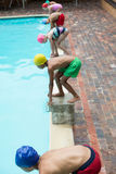 Children preparing to dive in pool. High angle view of children preparing to dive in pool Stock Photo