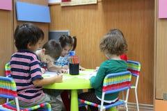 Children preschool to kindergarten. Children sitting at table and drawing in kindergarten in Bucharest,Romania Royalty Free Stock Image