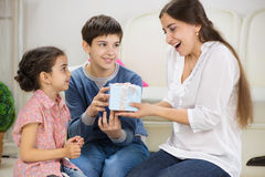 Children presenting a gift to mother. Cute children presenting a gift to mother royalty free stock photography
