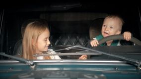 Children pretend driving car sitting on front vehicle seats.  stock video